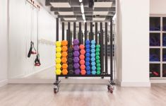 Stacks of colorful dumbbells in a gym weight rack