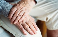 Close up of older man's hands folded in lap.