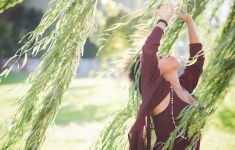 Woman looking and reaching up into boughs of willow tree.