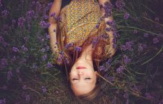 Woman lying on ground covered in purple flowers.