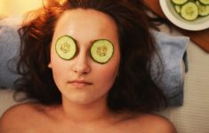 Woman laying on spa mat with cucumber slices over her eyes