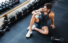 Man taking a break from working out in gym, sitting on floor drinking water.