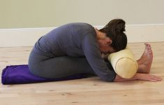 Woman using bolster and yoga props in seated forward bend.