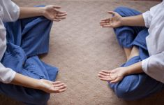 Two people yoga pose palms up on knees