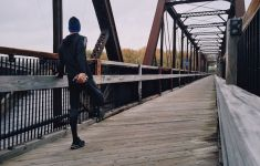 Man stretches on bridge before running