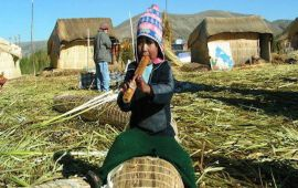 Bolivian child playing flute while sitting astride straw bale