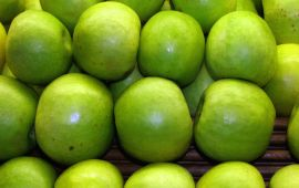 green apples stacked in rows