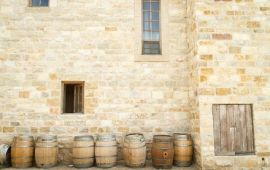 rustic back alley in Italy with row of wine barrels