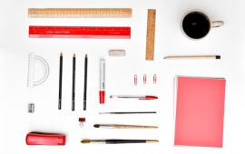 Perfectly aligned desk supplies on white desktop