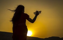Silhouette of girl playing with toy airplane against sunset golden sky