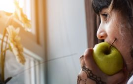 Close up of girl eating an apple while looking out the window