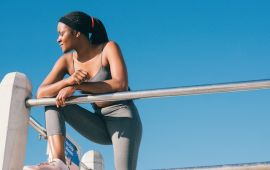 Woman in exercise clothes overlooking a railing.