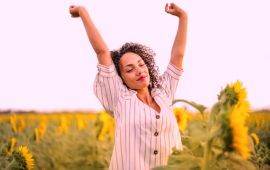 Woman in a field of sunflowers stretching toward the sky