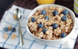 Blueberries in oatmeal in white bowl on white and blue towel with spoon.