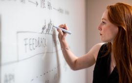 Woman writing about FEEDBACK on a whiteboard.
