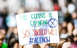A picket signs reads THE CLIMATE IS CHANGING SO SHOULD WE