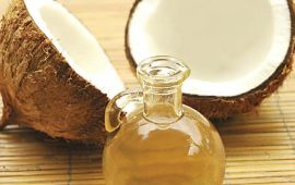glass bottle of coconut oil with coconut halves
