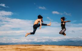 Couple jumping high in outdoors.