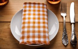 Orange gingham napkin with silverware and dinner plate setting.
