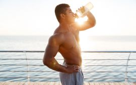 Shirtless man drinking water on pier by ocean.