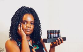 Woman holding up small bottles of oils while rubbing oil into her face