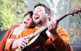 A father and son sing together while playing guitar