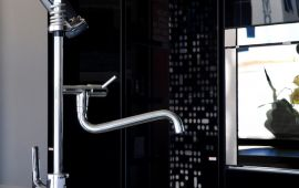 Modern chrome faucet against black wall and window.