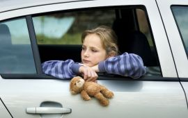 Sad girl looking out car window while holding teddy bear