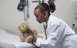 Girl with lab coat and stethoscope pretending to be doctor to a teddy bear