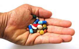 man's hand outstretched filled withe prescription pills and tablets