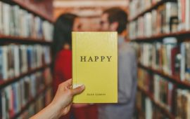 Book titled HAPPY held up in front of couple in library.