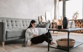 Woman sitting on her floor with laptop computer