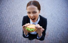 Very hungry businesswoman about to bite into sandwich