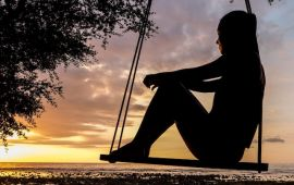 Silhouette of woman sitting on a swing at sunset.