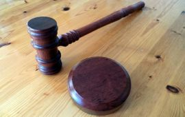 Judge's gavel and pad on wooden desk.