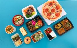 Several prepared meals and foods in containers arranged on turquoise table.