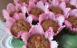 Healthy morning glory muffins arrange don green plate in pink wrappers.