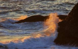 Ocean surf crashing against cliff at sunset