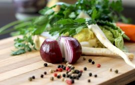 A red onion on cutting board with peppercorns and vegetables