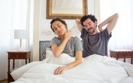 A couple in bed waking up and stretching.