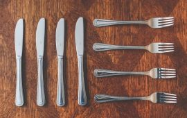 silverware knives and forks on wooden table