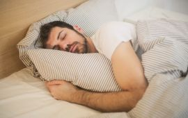 Man sleeping in bed with striped sheets