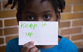 small girl holding up motivational message in front of her face