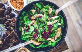 large bowl of spinach salad with chicken and pomegranate