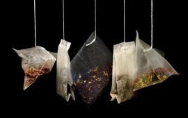 Five teabags hanging in front of black background.