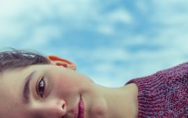Woman lying on side in front of blue sky
