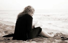Sepia tone of woman reading a book on the beach.