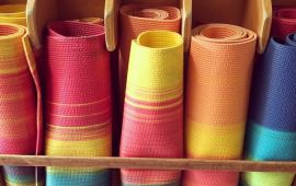 rainbow colorful rolled yoga mats in wooden rack