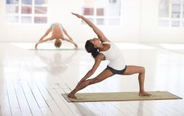 Man and woman doing asana poses in yoga studio.