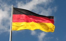 German flag fluttering in breeze with blue sky and clouds